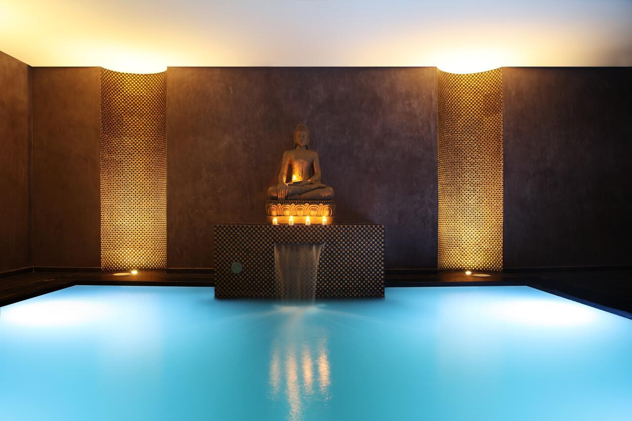 Spa con una pequeña cascada y una estatua de buda encima. Luz tenue y relajante.