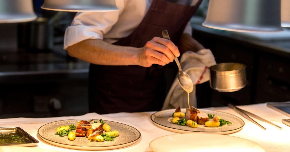 Chef preparando un plato hecho de carne y verduras. Esta echando salsa por encima de este.