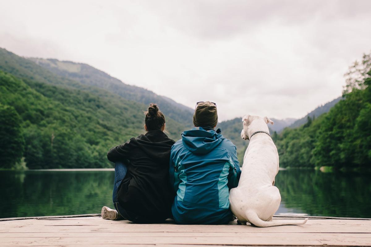 Pareja con su perro en un lago