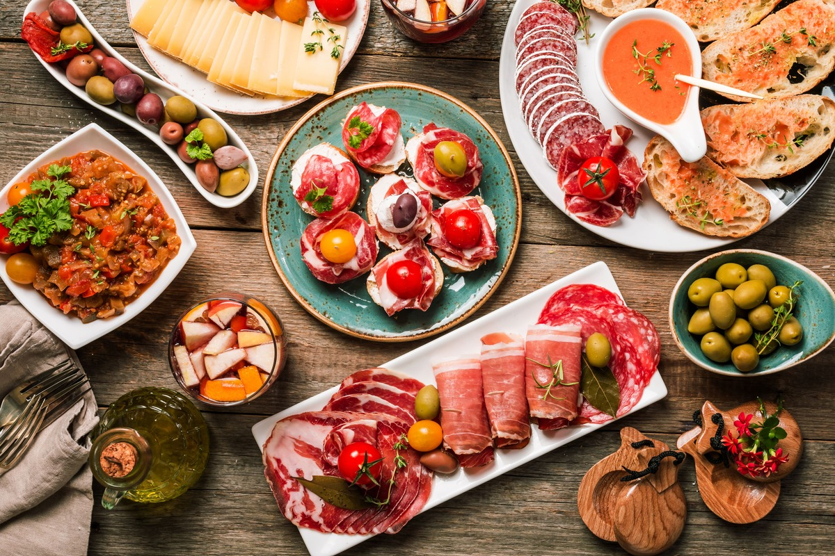 Mesa llena de platos de comida típica española. Podemos identificar platos como, pan con tomate, queso, olivas, jamón, gazpacho entre otros muchos