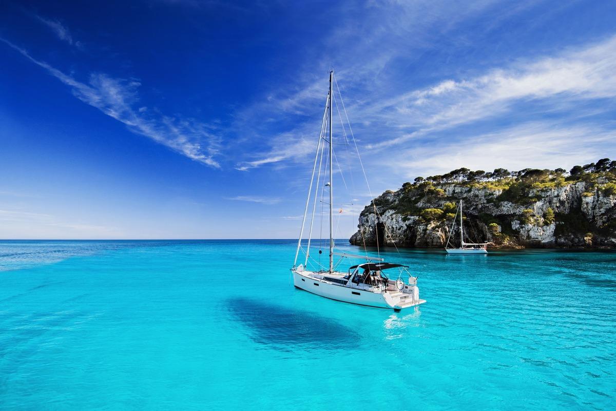 Playa de Mallorca con el agua cristalina azul celeste y un velero en medio del mar