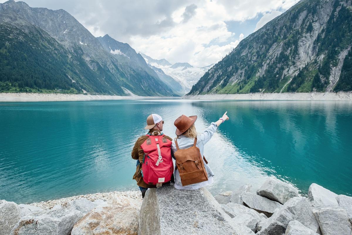 Pareja sentada de espaldas al espectador en la orilla de un lago rodeado por montañas