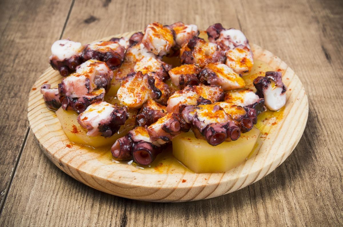 Plato de madera con uno de los platos típicos de galicia, pulpo a la gallega