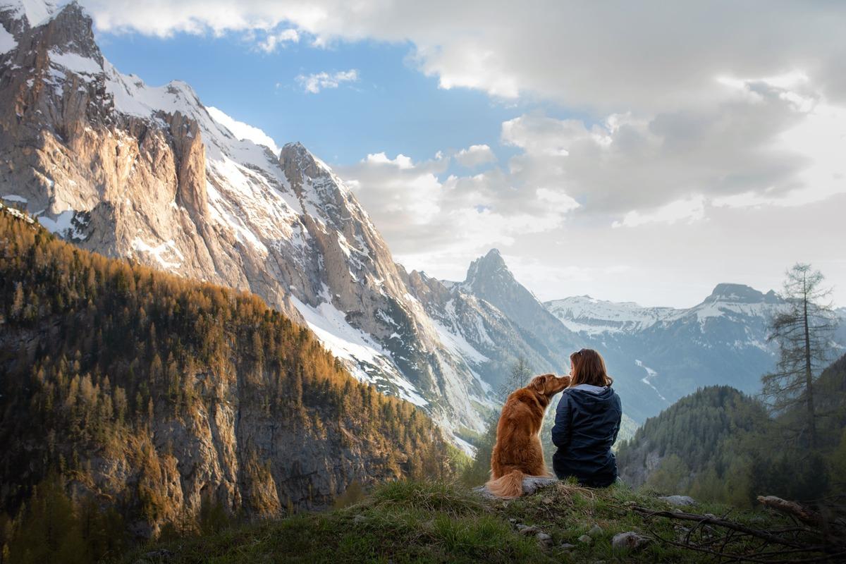 Montañas nevadas de fondo. En la parte frontal derecha, un perro lame a su dueña, ambos están sentados en una colina