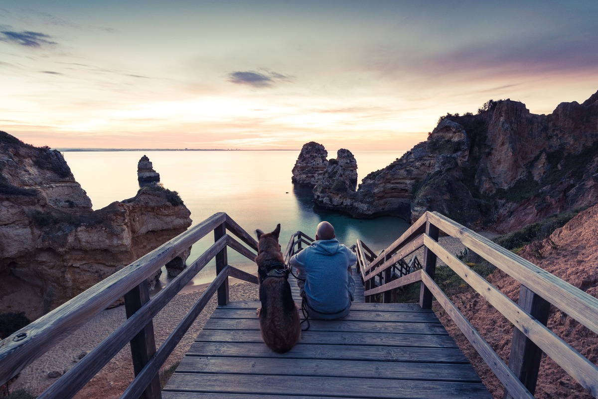 Atardecer en la playa de Lagos - Portugal. En la parte central hay unas escaleras de madera que bajan a la playa. En ellas hay sentados de espaldas al espectador un perro y su dueño