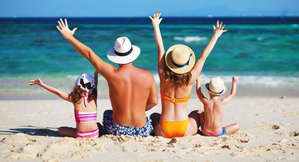 Familia en la playa sentada en a arena frente al mar