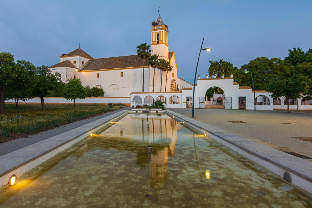 Santuario de Consolación en Utrera con un estanque en frente y una tardecer de fondo.