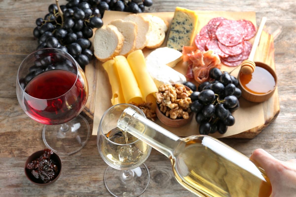 Mesa con una tabla de madera. En ella hay pan, queso, embutido, nueces, uvas y miel. En frente de esta hay dos copas de vino. Una de ellas con vino tinto y otra con vino blanco.