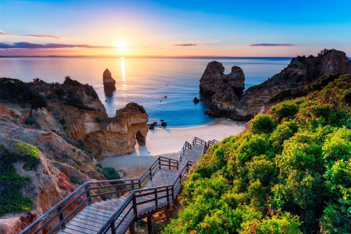 Playa con unas escaleras de madera que bajan al mar en Lagos, Algarve, Portugal.