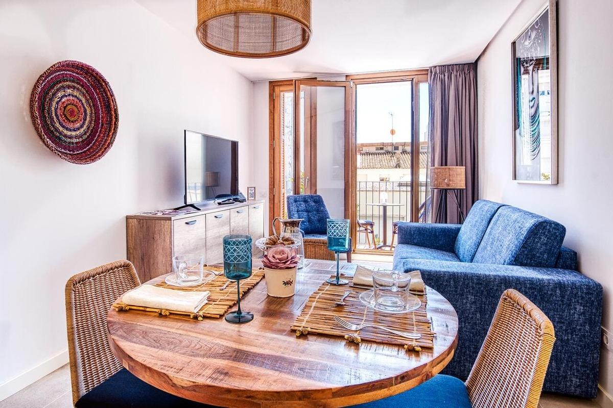 Comedor de un apartamento de playa. Mesa con cubertería en frente y sofás en el fondo.